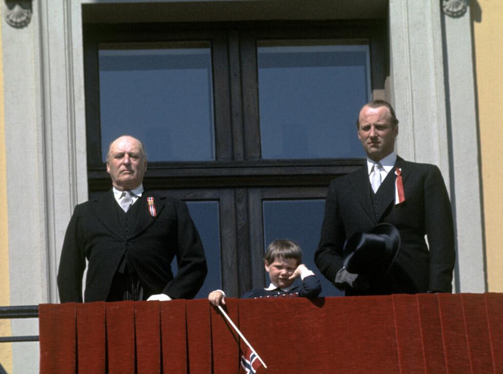 1977: Det er ingen tvil om at å vinke til folket fra slottsbalkongen på 17. mai kan bli en lang affære for de søte små. Her er en litt sliten fem år gamle prinsesse Märtha Louise fotografert mellom sin far kronprins Harald og bestefar kong Olav. Dette året var verken kronprinsesse Sonja eller prins Haakon på slottsbalkongen på 17. mai. Foto: NTB scanpix