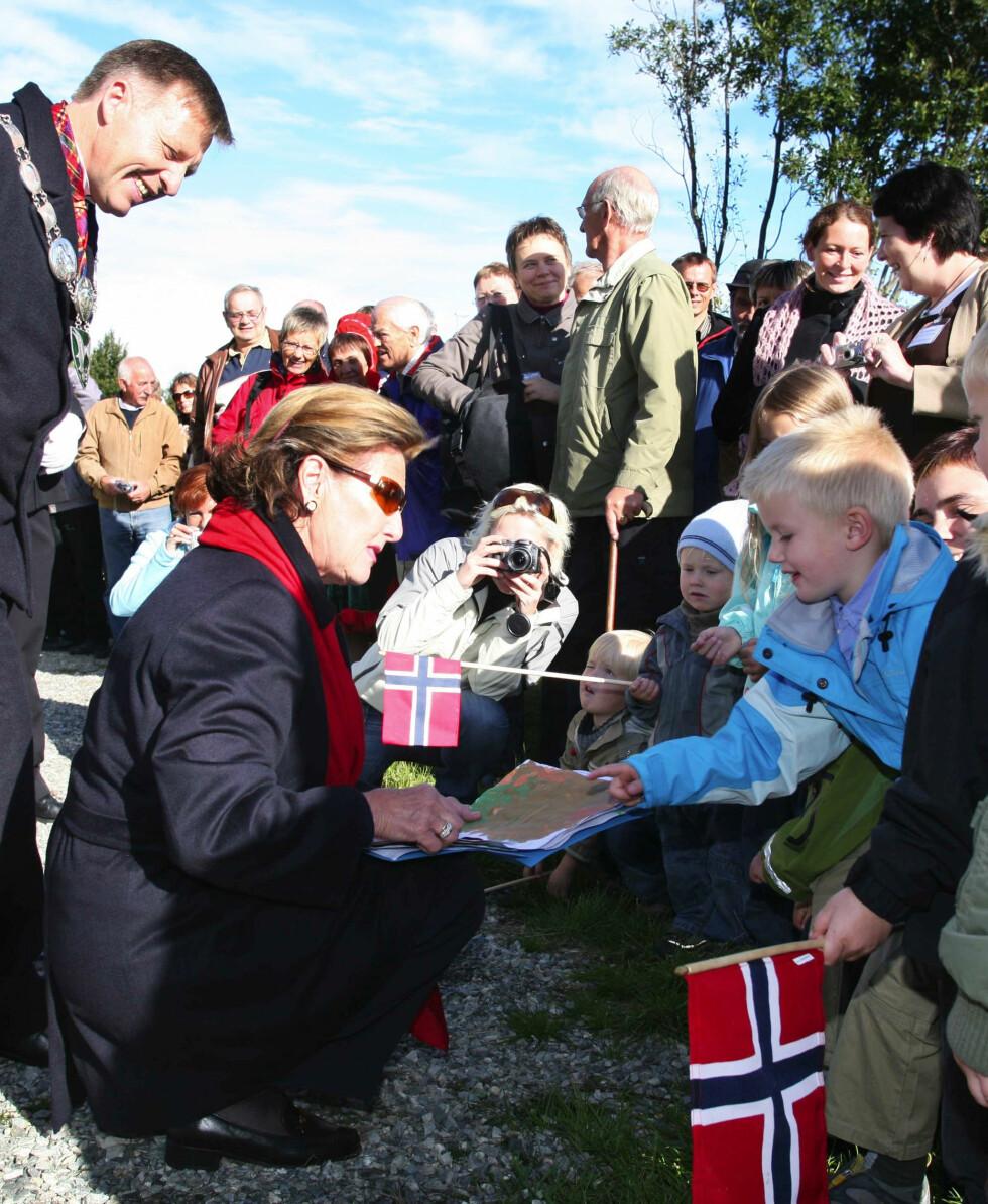NÆRKONTAKT: Dronning Sonja har alltid hatt en helt spesiell tone med barn. Her hilser hun på barna i Trollskogen Barnehave i Nordreisa som hadde malt høstbilder til den kunstinteresserte dronningen. Året er 1993. Foto:  Foto: Aftenposten via NTB Scanpix