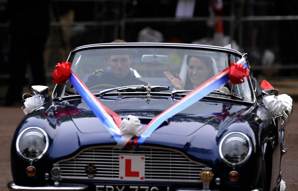 PRINSEN BAK RATTET: Det var prins William selv som kjørte sin nybakte hustru til deres felles hjem etter vielsen, og som seg hør og bør for et nygift par var bilen, en to-seter av typen Aston Martin DB6 Volante, pyntet med «JU5T WED»-skilt. Foto:  NTB Scanpix