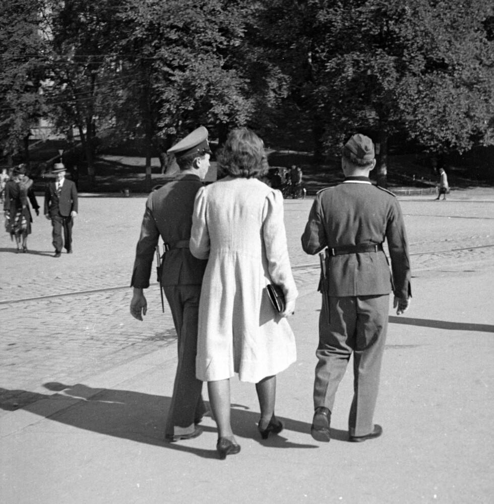 NORSK KVINNE + TYSK SOLDAT: De norske kvinnene (som var etter den ariske standard) ble oppfordret til å finne seg en tysk mann som de kunne få barn med. Dette bildet viser en norsk kvinne på tur i Oslo sentrum med to tyske soldater i 1940.  Foto: Ingvald Møllerstad  for Aftenposten / NTB Scanpix