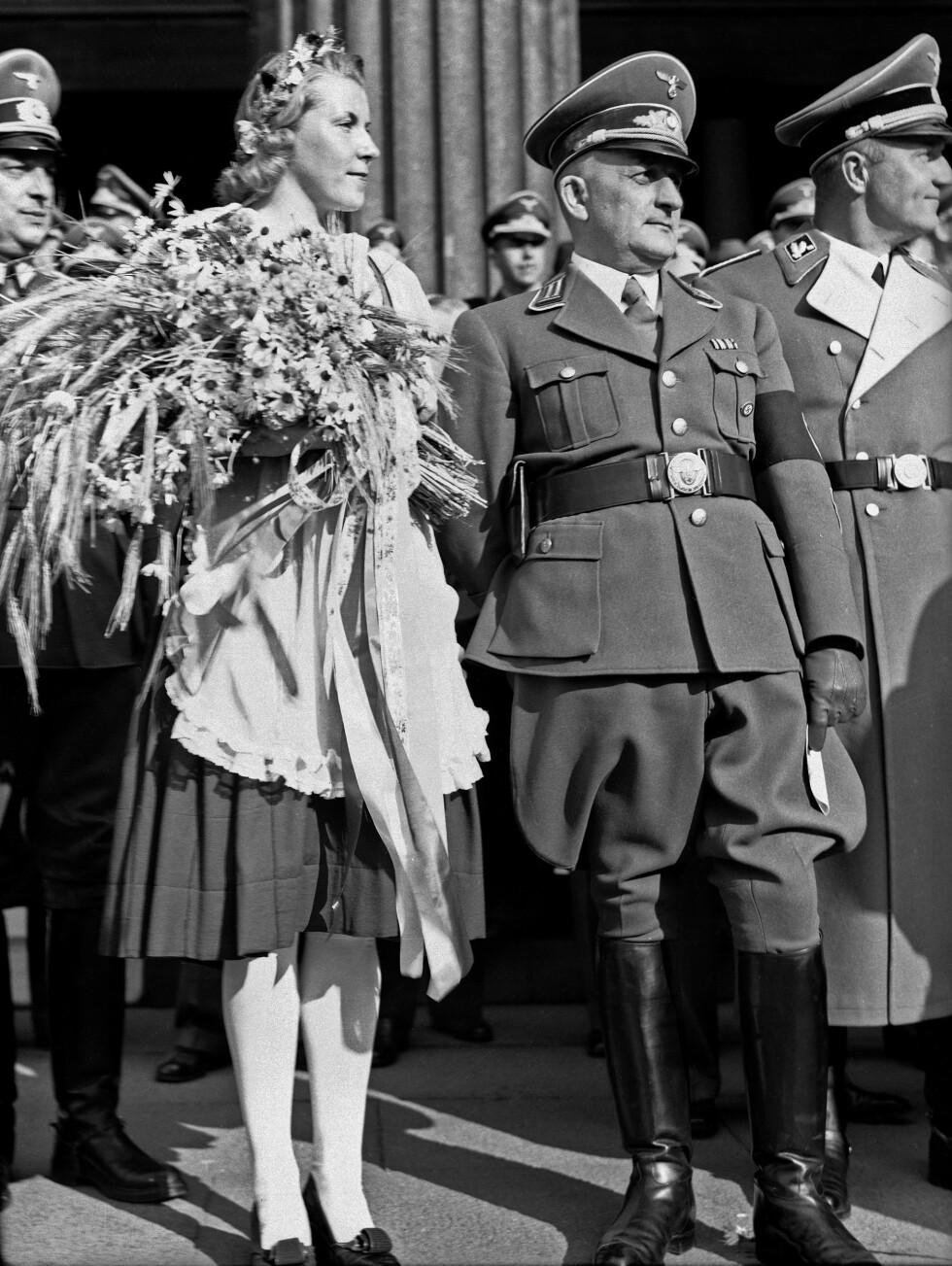SIDE OM SIDE: I 1941 ble det arrangert Høsttakkefest på Universitetsplassen i Oslo - og her er en tysk offiser fotografert side om side med en ukjent norsk kvinne.  Foto: NTB Scanpix