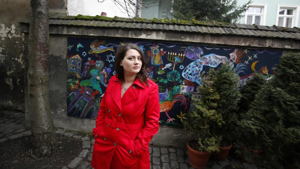 «SCHINDLERS LISTE»: Polske Oliwia Dabrowska var bare tre år da hun spilte «Den lille jenta i den røde kåpen» i filmen «Schindlers liste». Filmen hadde premiere i desember 1993, og 20 år etter poserte hun i jødekvartalet i Krakow - i nettopp en rød kåpe. Foto: Piotr Malecki / Panos Pictures / Felix Features