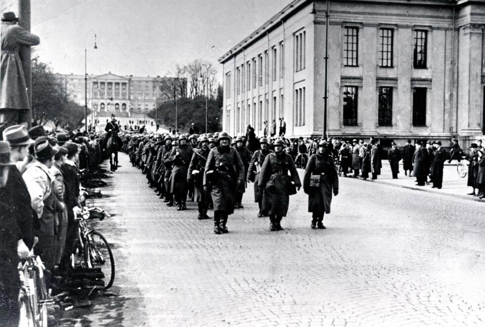 KARL JOHANS GATE: Dette bildet er tatt 9. april 1940 og viser tyske styrker som har inntatt paradegaten Karl Johans gate i Oslo. I bakgrunnen ser vi slottet - hvor kongefamilien noen timer tidligere hadde flyktet fra. Mannen med sykkel til venstre i bildet er for øvrig motstandskjempen Gunnar Sønsteby.  FOTO: NTB