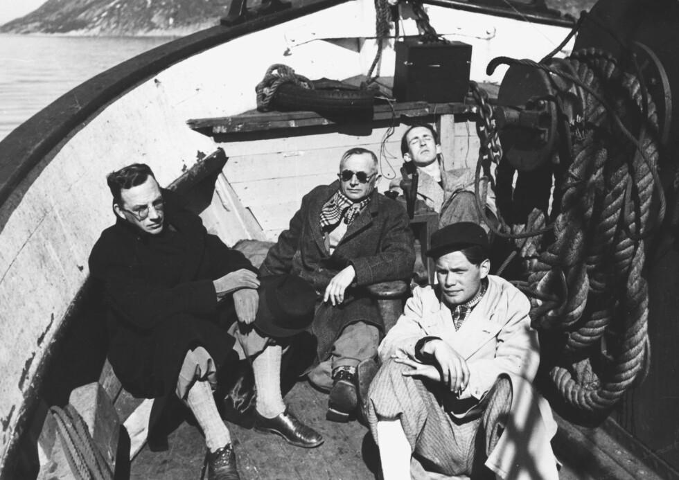 """PRESSEFOLK: NRKs og pressens folk om bord på båtene """"Reform"""" og """"Grimsøy"""" under flukten nordover, fra Ålesund til Bodø i april 1940. F.v.: Olav Larssen, Arbeiderbladet, Hans Amundsen (med solbriller), mannen i bakgrunnen er ukjent, forfatter og journalist Sigurd Evensmo, Arbeiderbladet (foran t.h.). FOTO: NTB"""
