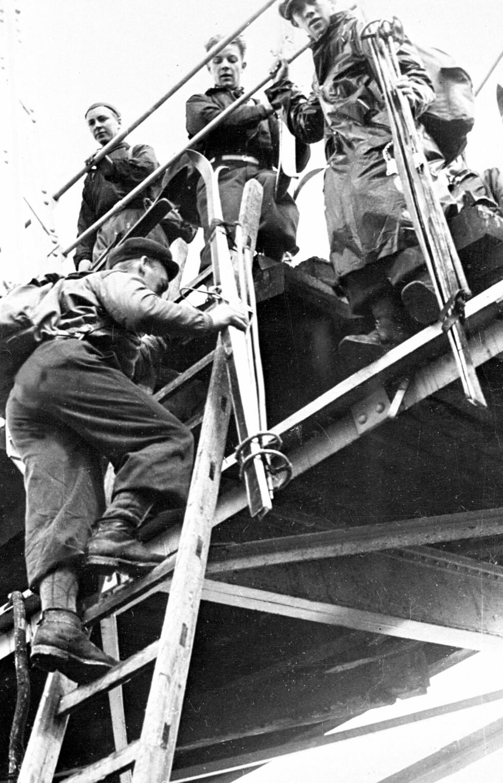 STERKE KARER: Mobiliseringen av norske soldater de første dagene etter invasjonen. Soldater som bærer på ski tar seg over ødelagte broer til mobiliseringsplassen. Foto:  Foto: NTB scanpix