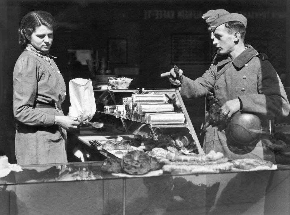 I MØTE MED FOLKET: Dette bildet er tatt på ukjent sted i Norge den 22. april 1940. Tyske soldater hadde allerede rukket å gjøre entre i bybildet. Her gjør to tyske soldater innkjøp i en bakerforretning, og blir ekspedert av en ung kvinne. Foto:  Foto: NTB scanpix