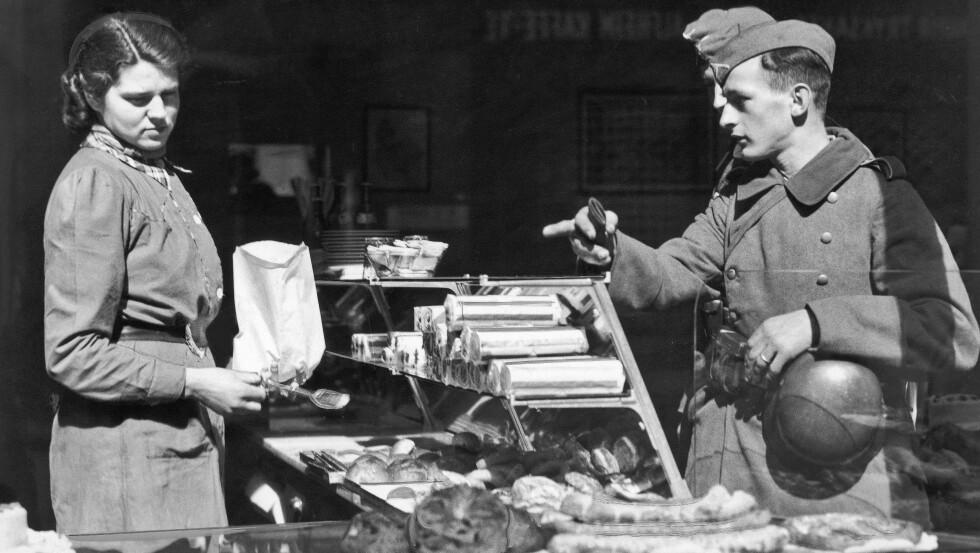 ANDRE VERDENSKRIG: Dette bildet er tatt på ukjent sted i Norge den 22. april 1940. Tyske soldater hadde allerede rukket å gjøre entré i bybildet. Her gjør to tyske soldater innkjøp i en bakerforretning, og blir ekspedert av en ung kvinne. FOTO: NTB