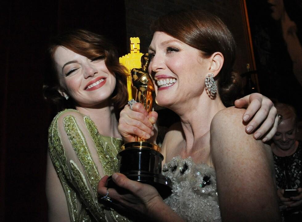 ALL GRUNN TIL Å SMILE: Tenk å ta med seg en statuett OG en goodiebag til 2 millioner kroner? Eller hva, Emma Stone og Julianne Moore? Foto: Afp