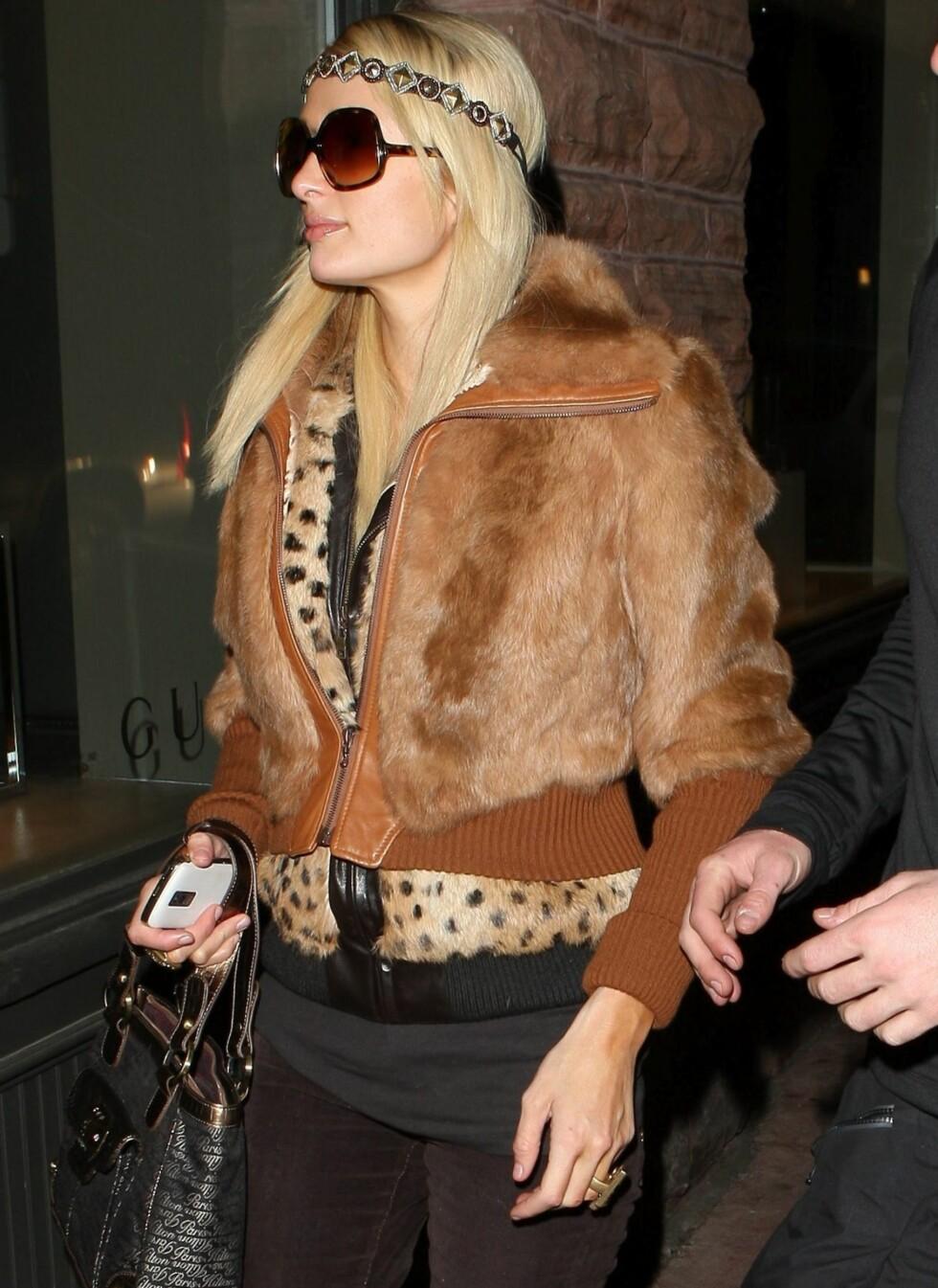 Paris Hilton klarer å kjøre den vante, dyriske stilen sin selv om kulda biter. Her er hun ikledd en brun jakke i pels over en leopardmønstret jakke.  Foto: All Over Press
