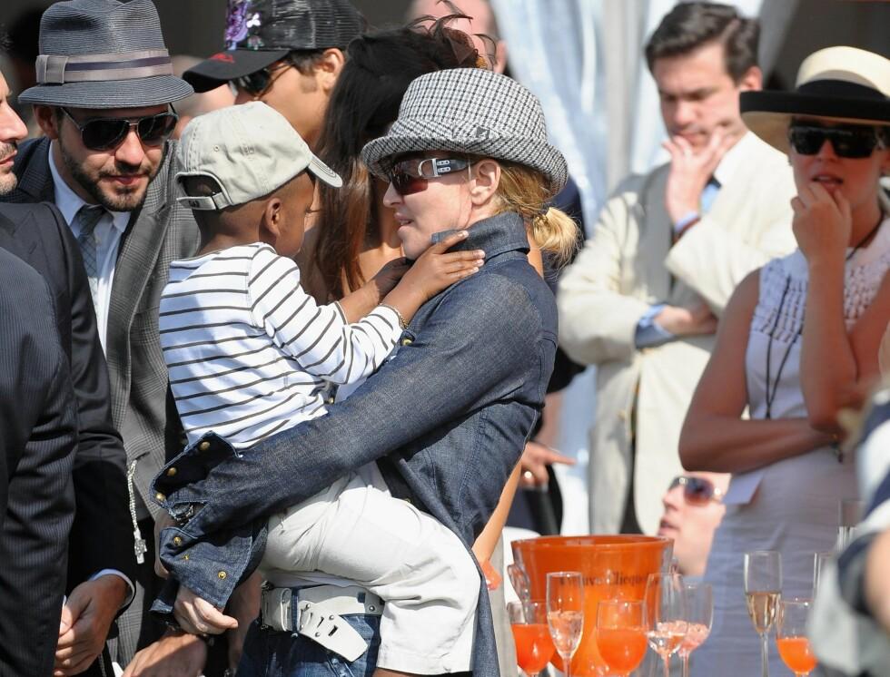 FÅR TID TIL DET MESTE: Trebarnsmor og artist Madonna trener to timer daglig seks ganger i uken. Innimellom tar hun seg tid til å gå på champagnefest med sønnen David Banda, som her. Foto: All Over Press
