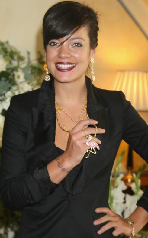 DESIGNER EGNE SMYKKER: Popstjernen Lily Allen elsker ikke bare å gå i lekre smykker - hun designer dem også. Her viser hun fram  et glitrende gullkjede med flamingoanheng på lanseringen av sin siste kolleksjon i London 27. juli. Foto: All Over Press