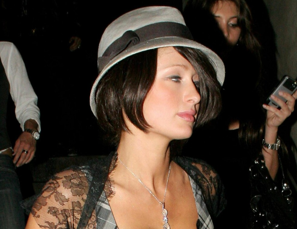 Hotellarving Paris Hilton klarer på mystisk vis å gå fra kort hår til langt hår i løpet av en uke. Hva kan det skyldes? Her er hun ute på tur i West Hollywood med både mørk pasjeklippet parykk og hatt på hodet.  Foto: All Over Press