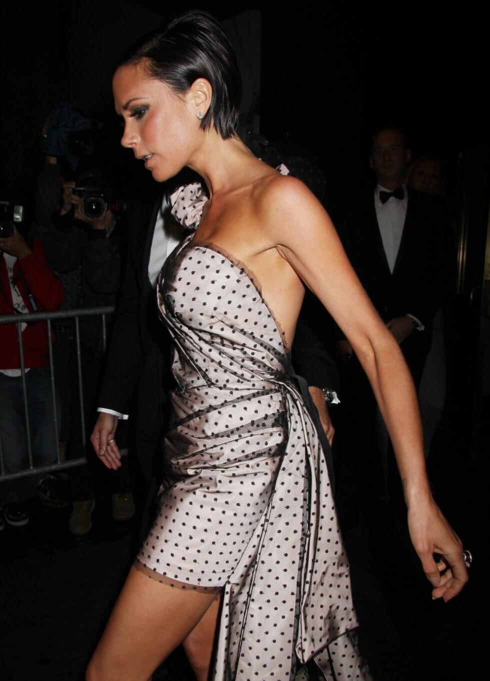 Victoria Beckham i prikkete kjole som både vil være kostymedrama og minikjole på en gang. Foto: All Over Press