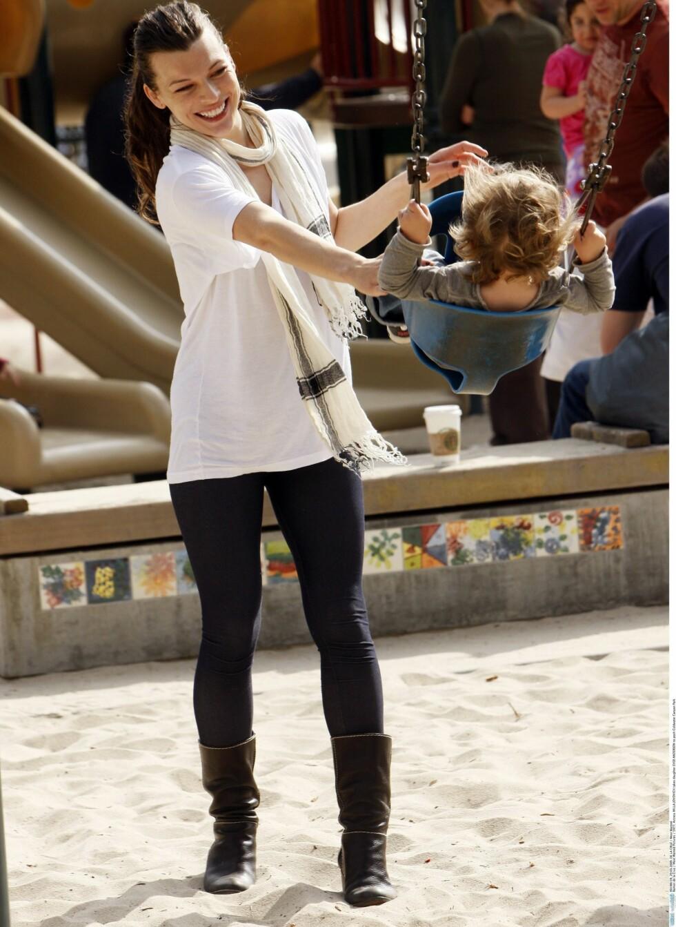 TIL TIGHTS: Supermodell Milla Jovovich bruker t-skjorten som kjole over tette strømper og slitte boots. Foto: All Over Press