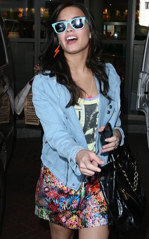 <strong>I 80-TALLSSTIL:</strong> Skuespiller Demi Lovato i fargerikt silkeskjørt som er pyntet ned med slitt olajakke og rocka t-skjorte. Legg merke til de turkise solbrillene. De er sommerens store slager!  Foto: All Over Press