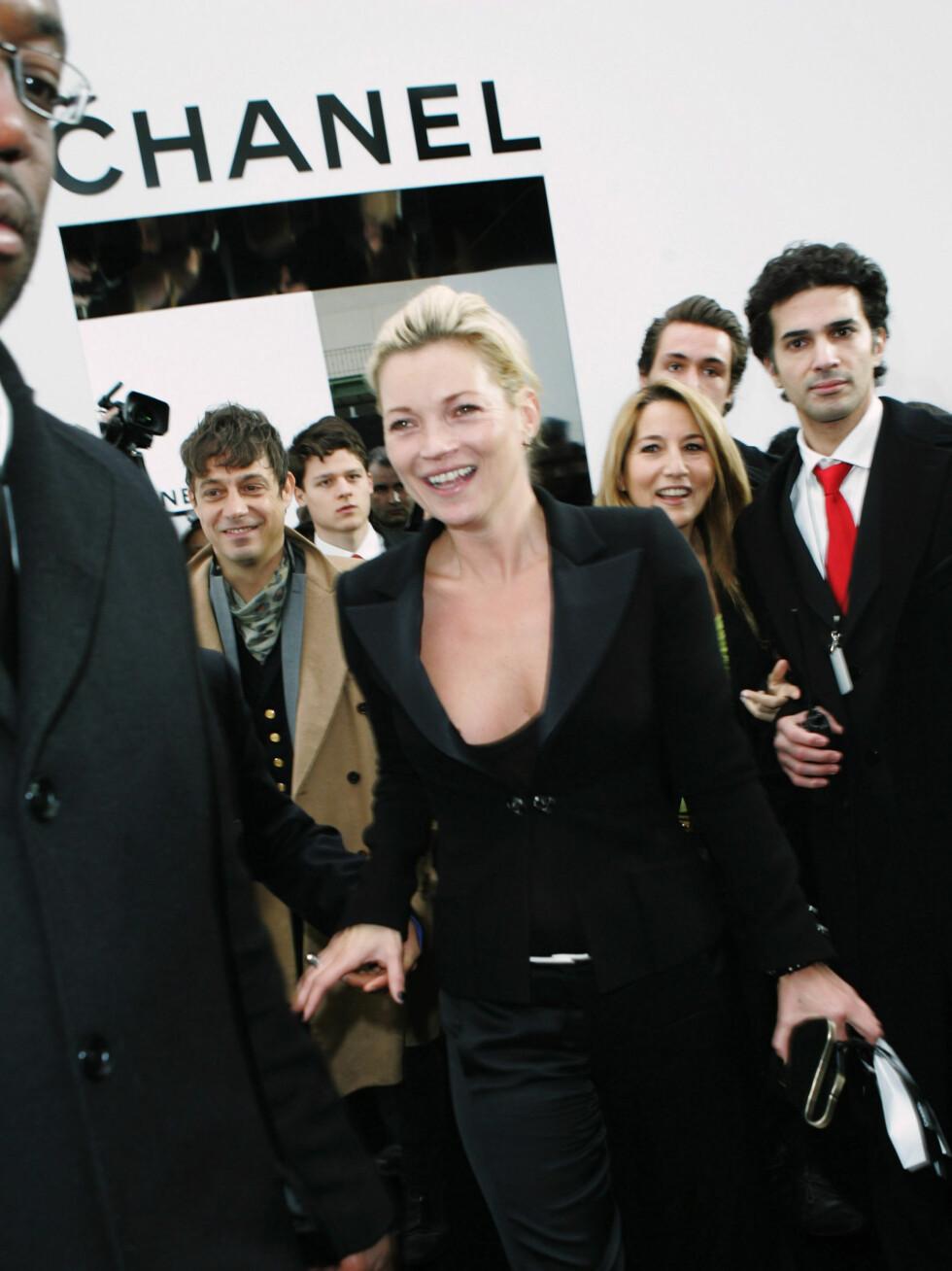 ET STORT SMIL: Kate Moss stilte i svart stilren klassisk dress på Chanels visning på Grand Palais i Paris. Foto: All Over Press