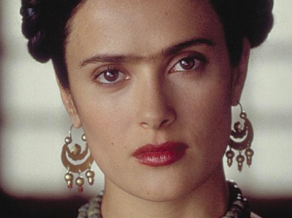 Den meksikanske maleren Frida Kahlo (her spilt av Salma Hayek) er nesten like kjent for sine sammenvokste øyenbryn og hårete overleppe som sin kunst. Foto: All Over Press