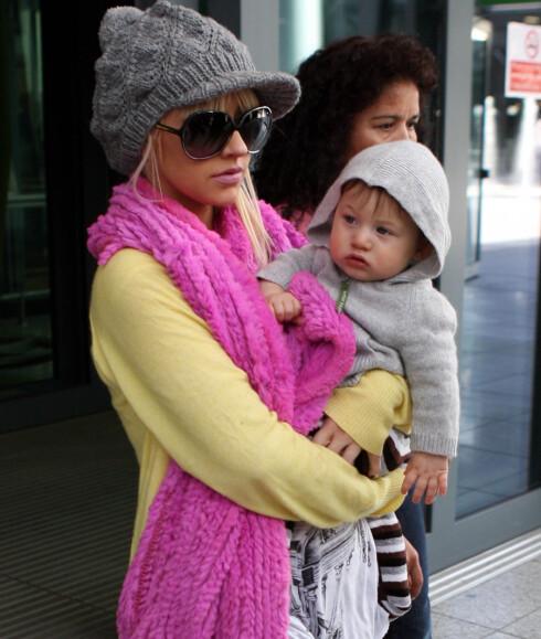Popstjerne Christina Aguilera innsvøpet i et knall rosa ullskjerf.