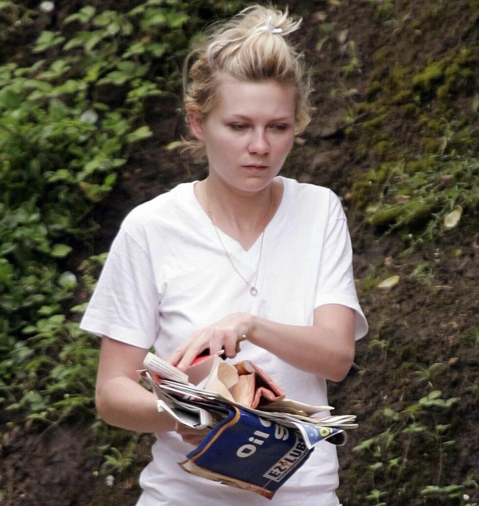 Skuespiller Kirsten Dunst ser morgengretten ut her, hvor hun henter posten med søndagsfrisyre og t-skjorte.  Foto: All Over Press