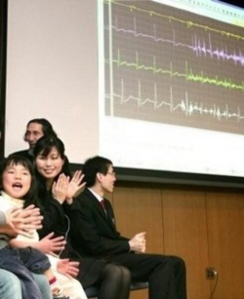 Professor Yoji Kimura (stående i bakgrunnen) demonstrerer hvordan lattermaskinen virker. Testpesonene har sensorer festet på kroppen og maskinen måler antall aH, altså latterbevegelser. (AFP)