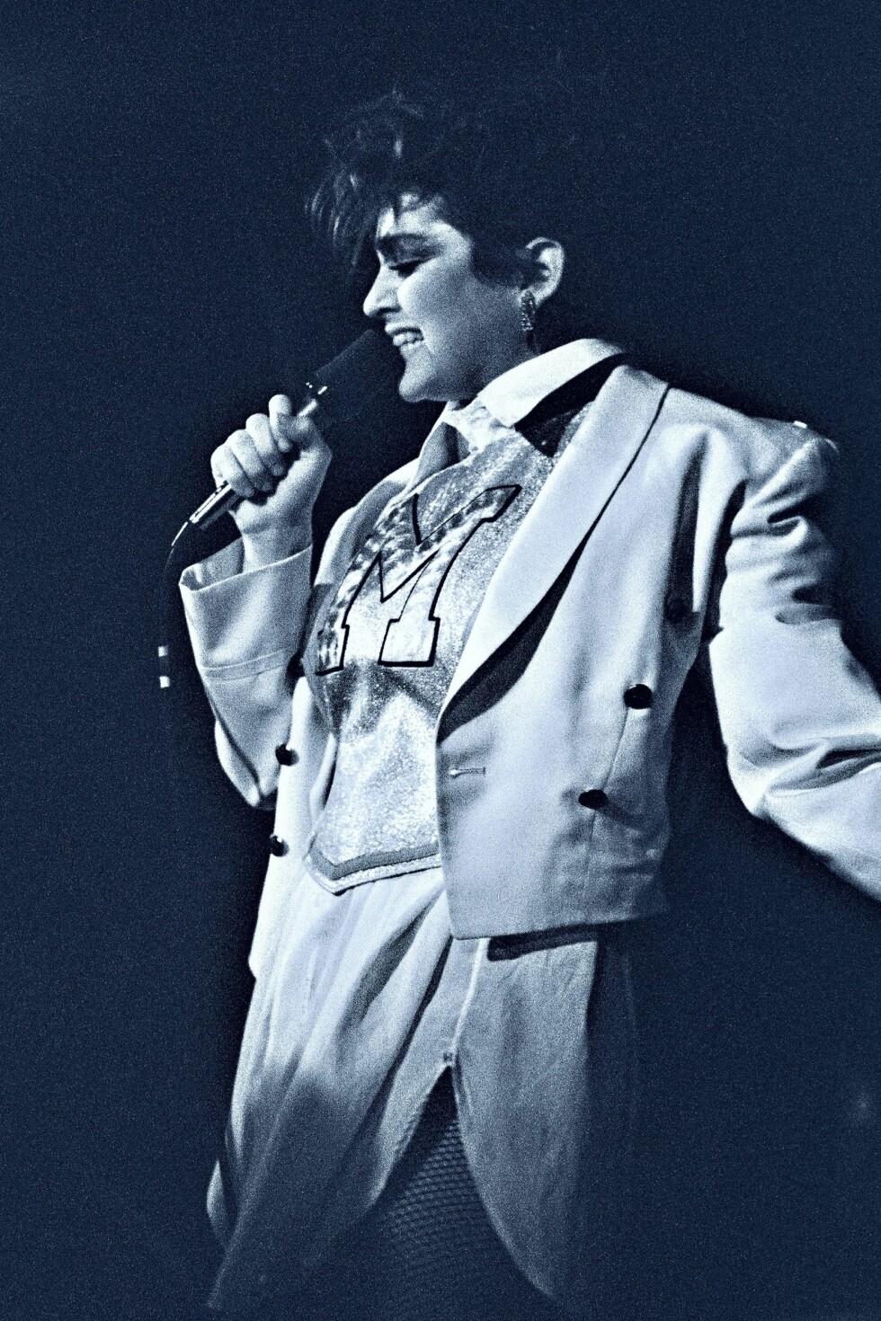 Det er ikke en Elvis-parodi, det er derimot Madonna, frontfigur i bandet Breakfast Club, som hun spilte med på midten av 80-tallet. Madonna begynte sin karriere som trommis i Breakfast Club.
