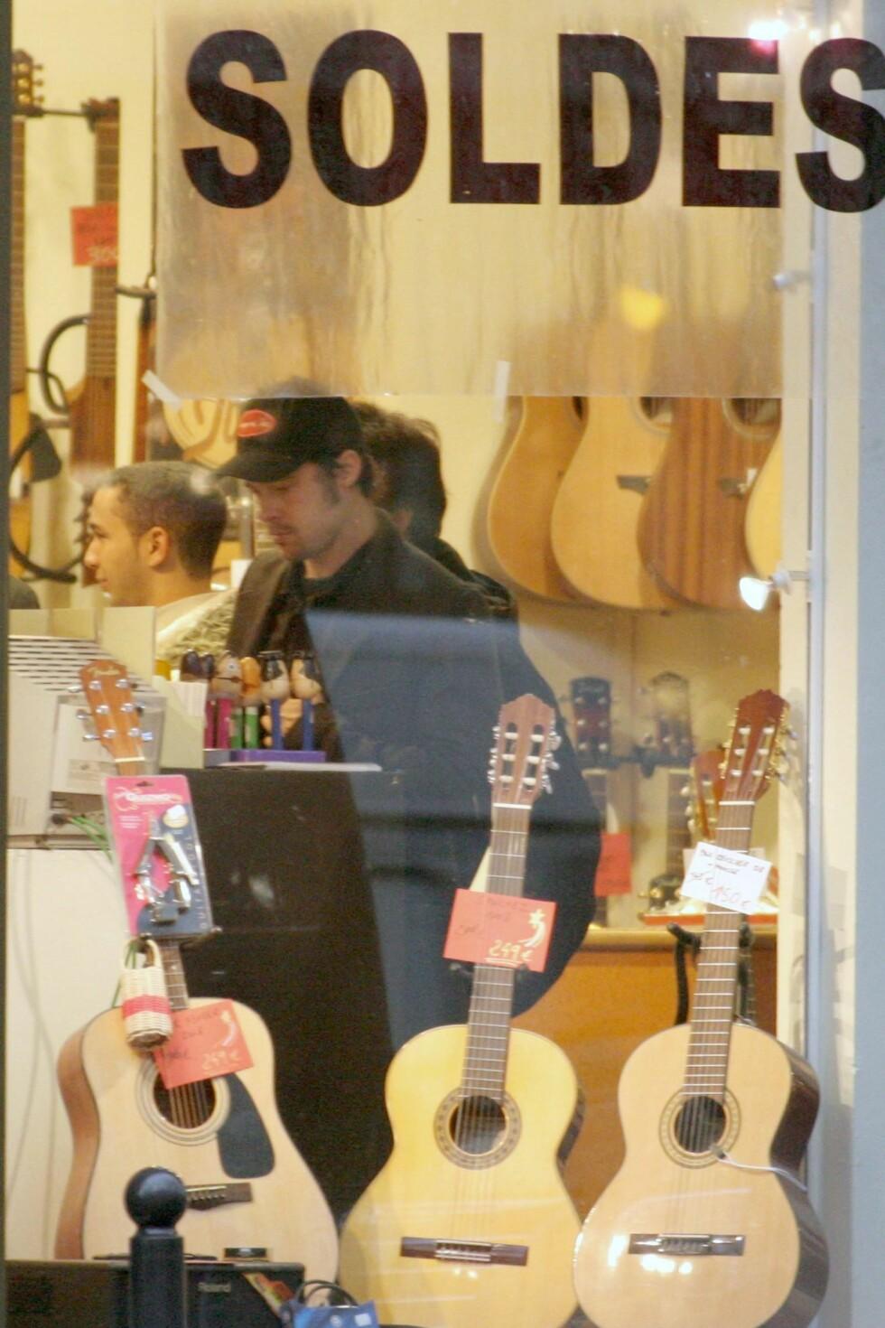 Skuespiller og vordende far Brad Pitt i Paris med Angelina Jolie. Her unner han seg fem minutter til gitarshopping.
