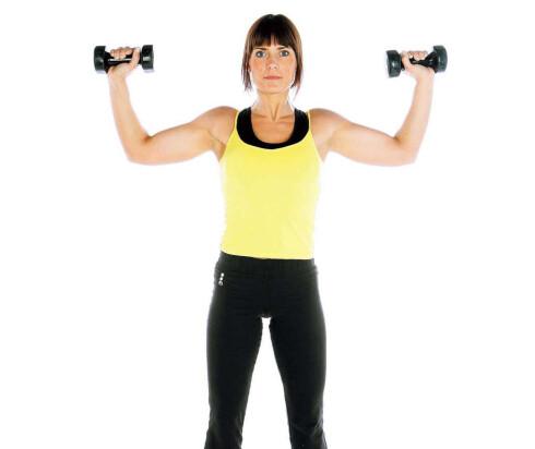 ØVELSE 1:  Stående manualpress. Stå med beina godt plassert i gulvet, spenn magen og finn balansen. Start bevegelsen med manualene plassert mellom skulderhøyde og ørehøyde, cirka 10 cm utenfor skuldrene. Press manualene opp til albueleddene er rette eller lettbøyde. Kom tilbake til startposisjonen og gjenta.