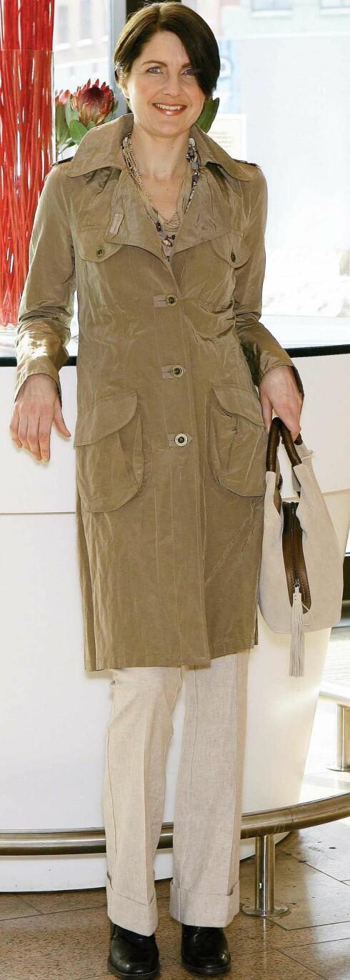 Sporty frakk i blankt, skinnende materiale (kr 1800) med utenpålommer med klaffer og brede slag. Veske med brun hank og glidelåsmarkering (kr 1000, begge fra Mexx).