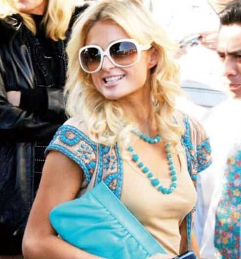 Paris Hilton med Farrah Fawcett-inspirert frisyre og turkise detaljer.