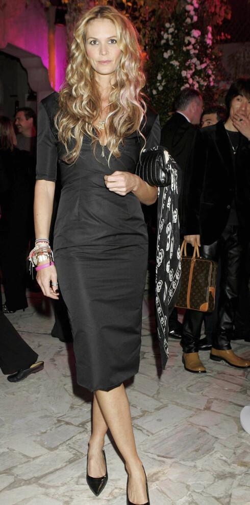 Modellen Elle Macpherson har skjerf med dødninghoder knytet på vesken. Silig.