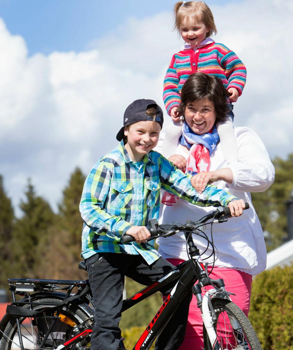 – Søsken normaliserer dagliglivet. Det er sunt at ikke alt dreier seg om hjertebarnet i en familie, sier Mette-Lise, her med Anine på skuldrene. Lars-Henrik har sykkel med elektrisk motor for å takle motbakkene.