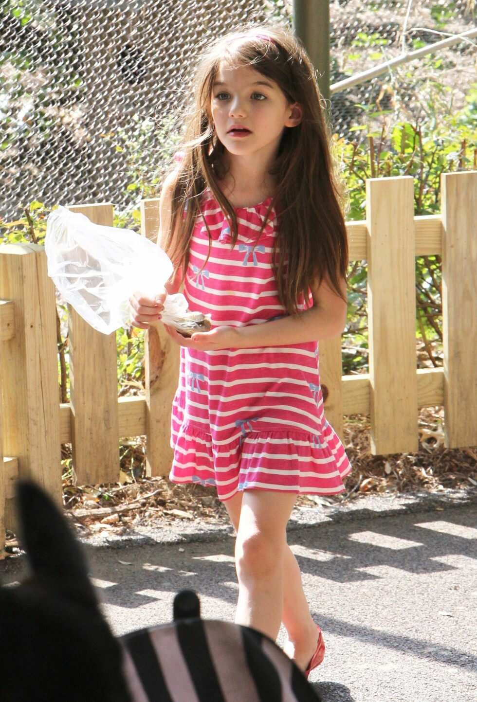 Lille Suri i stripete, rosa kjole og løst hår. Foto: All Over Press