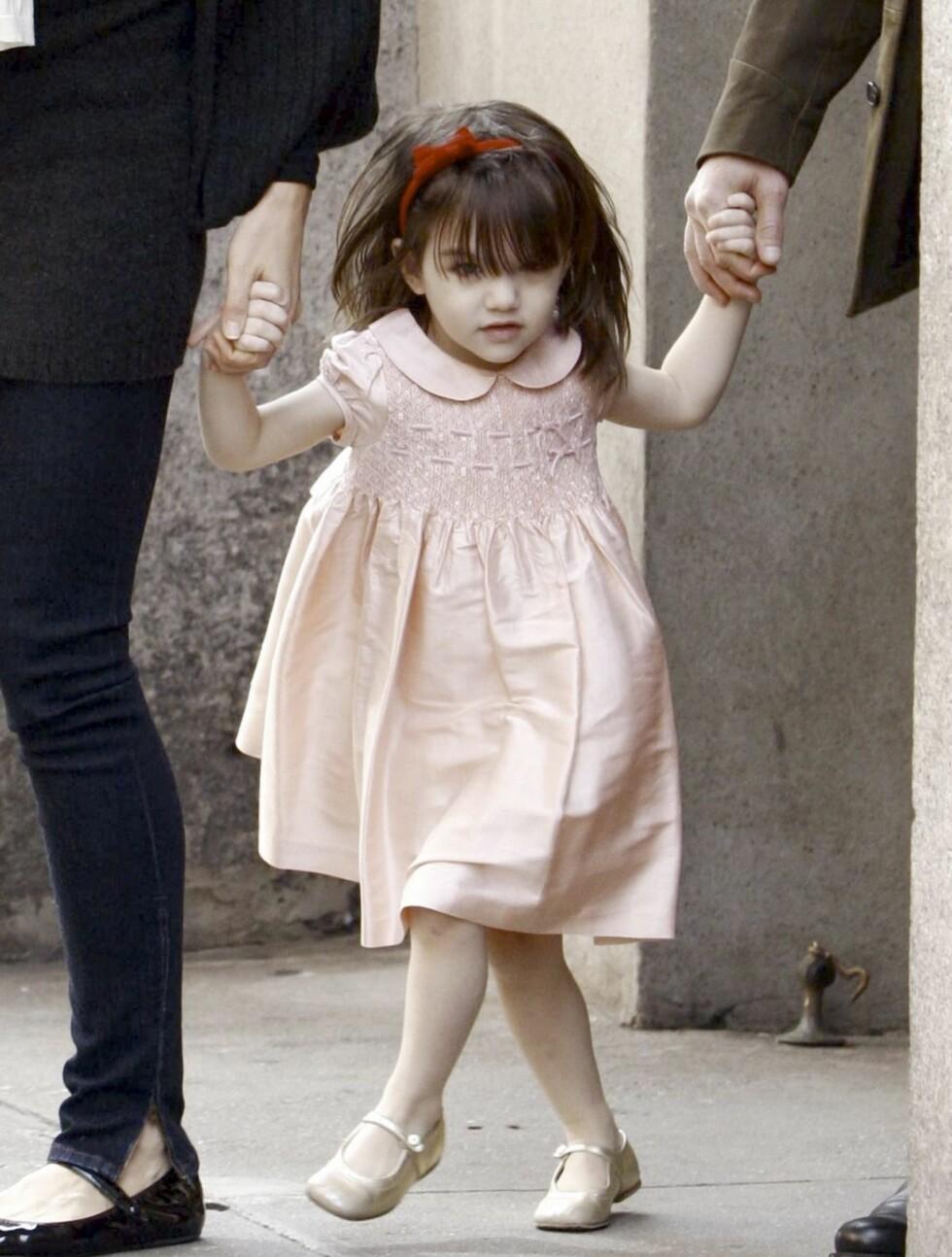 Lille Suri i lyserosa prinsessekjole og rødt hårbånd. Foto: All Over Press