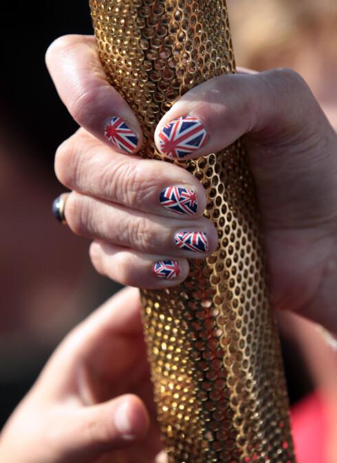 TIDLIG UTE: Sarah Blight hadde dekorert neglene med Union Jack allerede i mai. Her poserer hun med den olympiske ilden drøye to måneder før OL begynte.  Foto: All Over Press