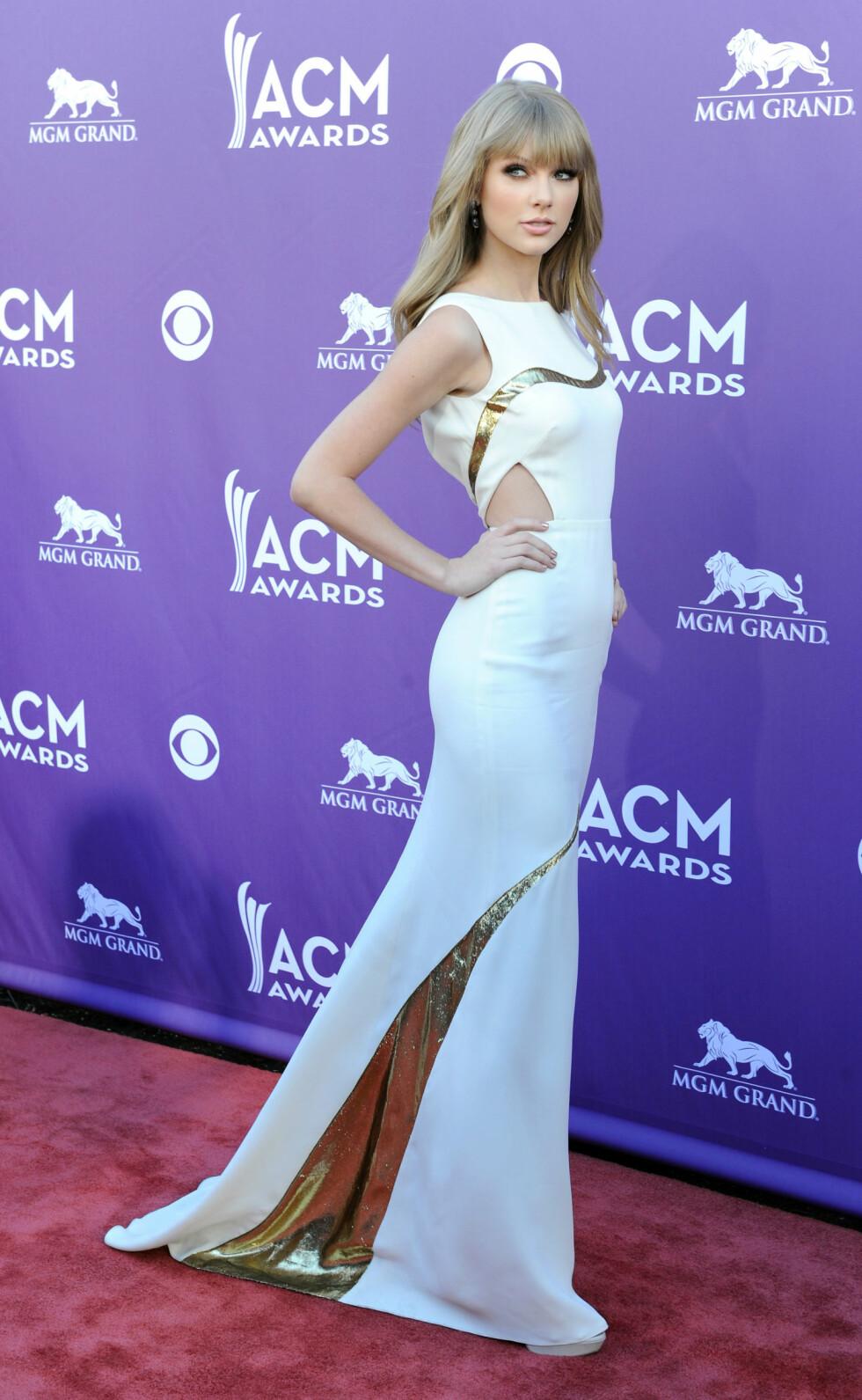 Slik kan det også gjøres. Gullfargen er detaljen som gjør kjolen til artist Taylor Swift mer interessant. Foto: All Over Press