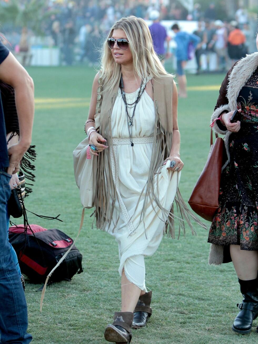 Popstjerne Fergie på festival i hvit hippieinspirert kjole, beige frynsevest og cowboyboots.  Foto: All Over Press