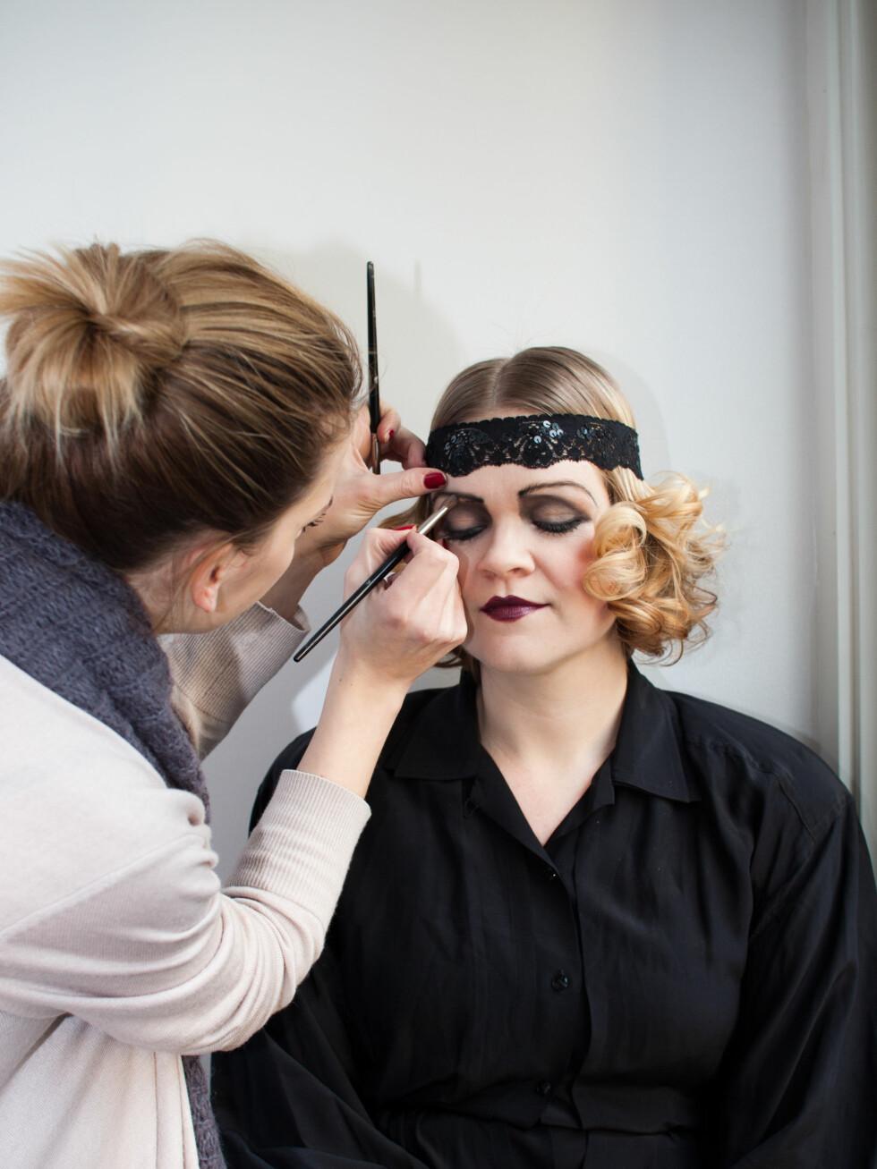 Makeupassistent Carina Marwell finjusterer sminken. Øynene skal se triste og melankolske ut, så linjene bues kraftig ned i ytterkant.  Foto: Kristin Hove