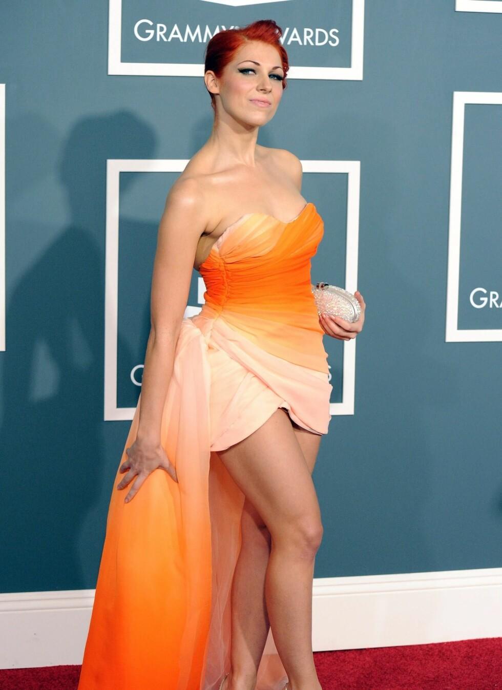Sanger Bonnie McKee i oransje kjole med langt slep.  Foto: All Over Press