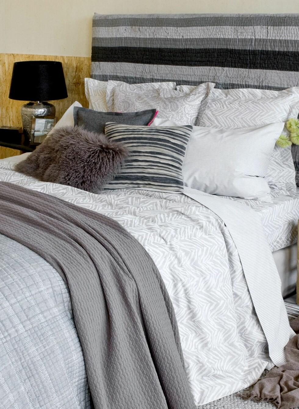 Fuskpelsputer og flere nyanser av grått og hvitt gjør seg også på soverommet. Foto: Ellos / Zara Home