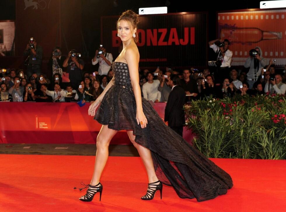 PROM QUEEN: Jessica Alba kledte seg i en kjole som var kort foran og lang bak da hun gjestet filmfestivalen i Venezia nylig. Hva synes du om hockey-kjolene? Stem i pollen under. Foto: All Over Press