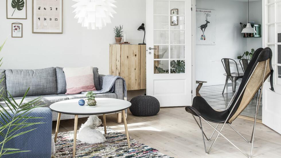 DRØMMEHJEMMET: Sofa fra Ikea, lenestolen er en Flaggermus-stol og sofabordet er fra Via Cph. Den strikkede puffen er fra Kvickly og lampen fra Normann Copenhagen. Lignende gulvteppe kan kjøpes hos Hay.  Foto: Frederikke Heiberg