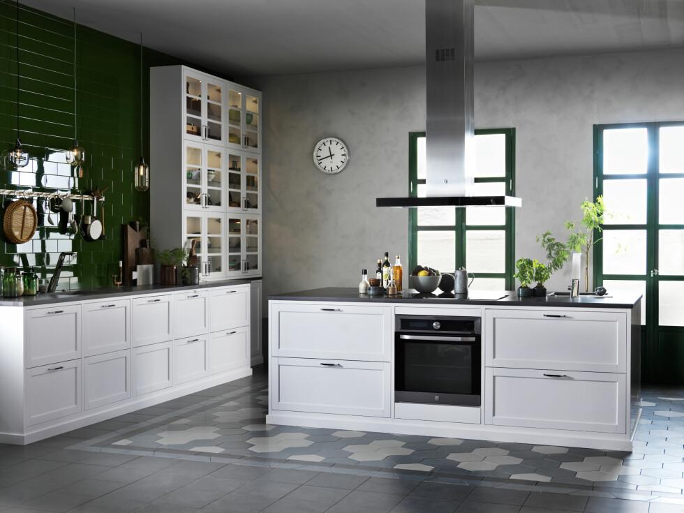 GRØNNE DETALJER: Det tradisjonelle, hvite kjøkkenet med profiler fra Drømmekjøkkenet vitaliseres av de grønne veggflisene og moderne detaljene. Klart du skal ha store, grønne planter på kjøkkenet også! Det gir liv, friskhet og sommerfølelse. Foto: Bulls