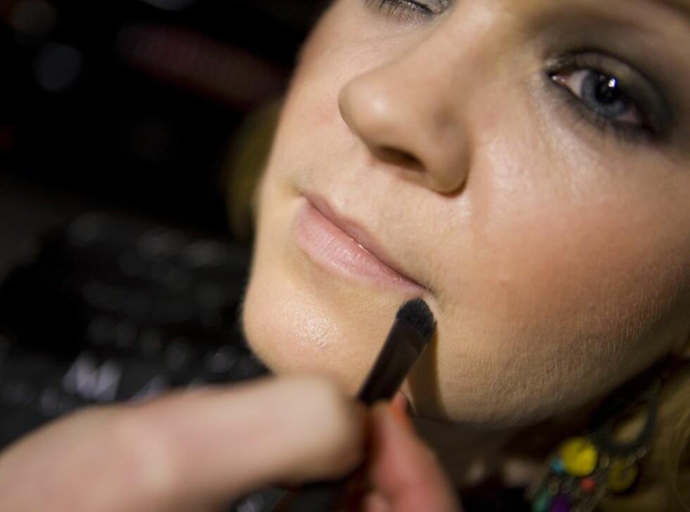 For å starte med et nøytralt utgangspunkt, legger makeupartisten foundation på leppene.  Foto: Per Ervland