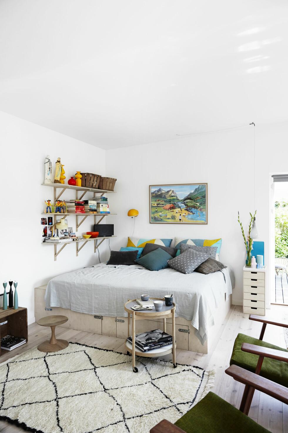 SOVESOFA: I stuen fungerer sofaen også som seng. Anders har snekret den selv, og uttrekksuffene inneholder sengetøy.  Foto: Birgitta Wolfgang/Sisters Agency