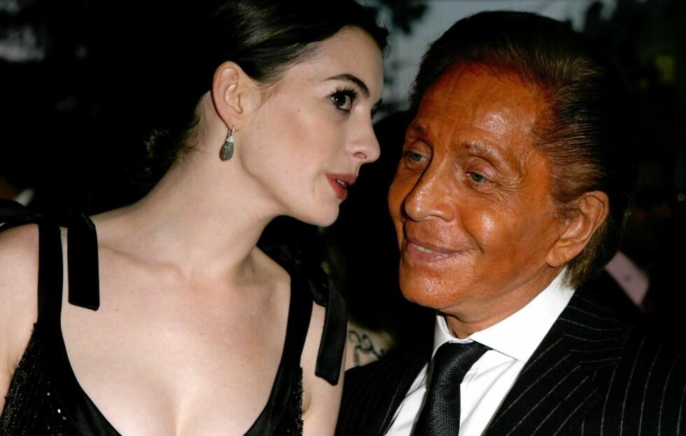 Hvis Anne Hathaway lener seg noe nærmere nå, er det fare for at hun får orange flekker på nesa fra Valentino. Foto: All Over Press