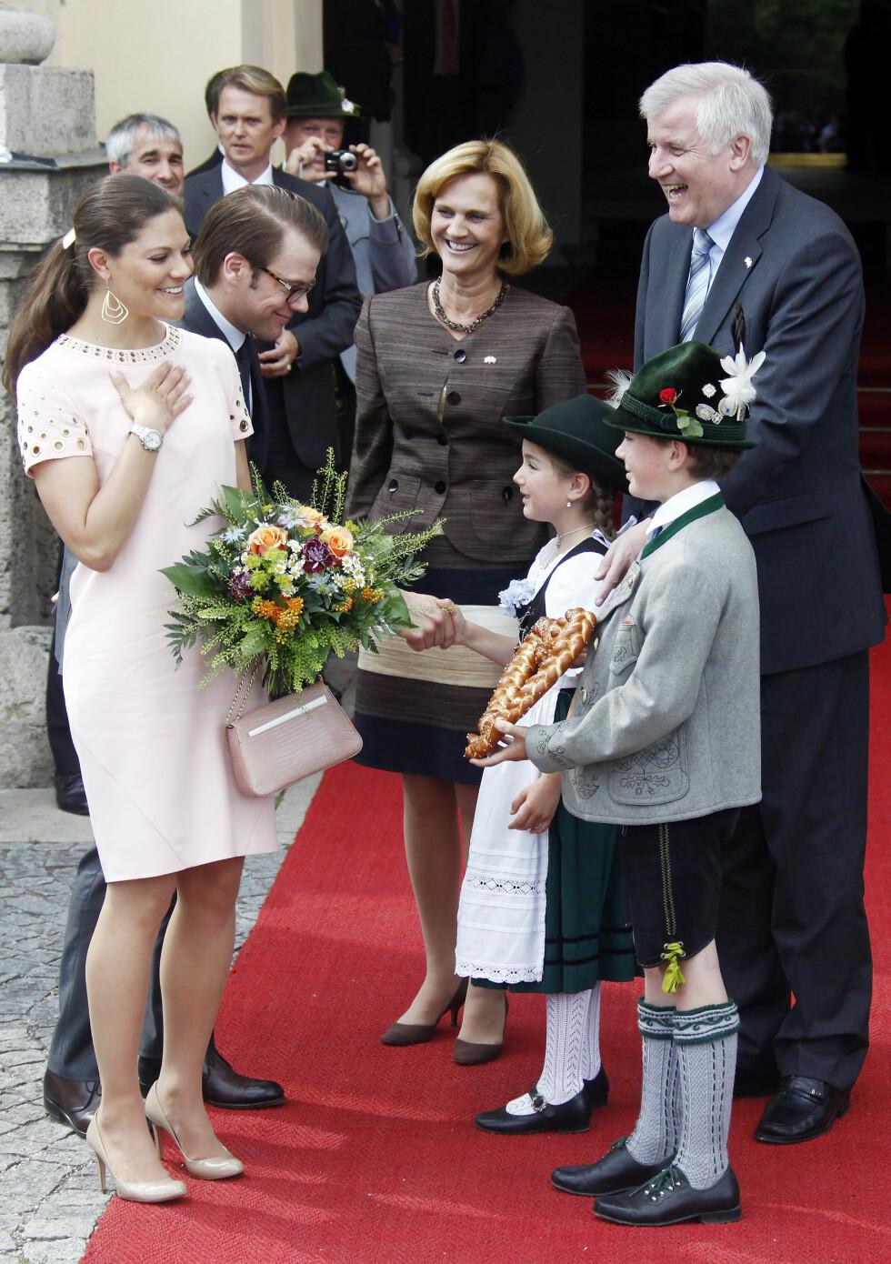 I TYSKLAND: Kronprinsesse Victoria og ektemannen prins Daniel hilste på barn i tradisjonelle klær under et besøk i München i Tyskland i 2011. I bakgrunnen er statsminister Horst Seehofer av Bayern og hans kone Karin. Foto: NTB Scanpix