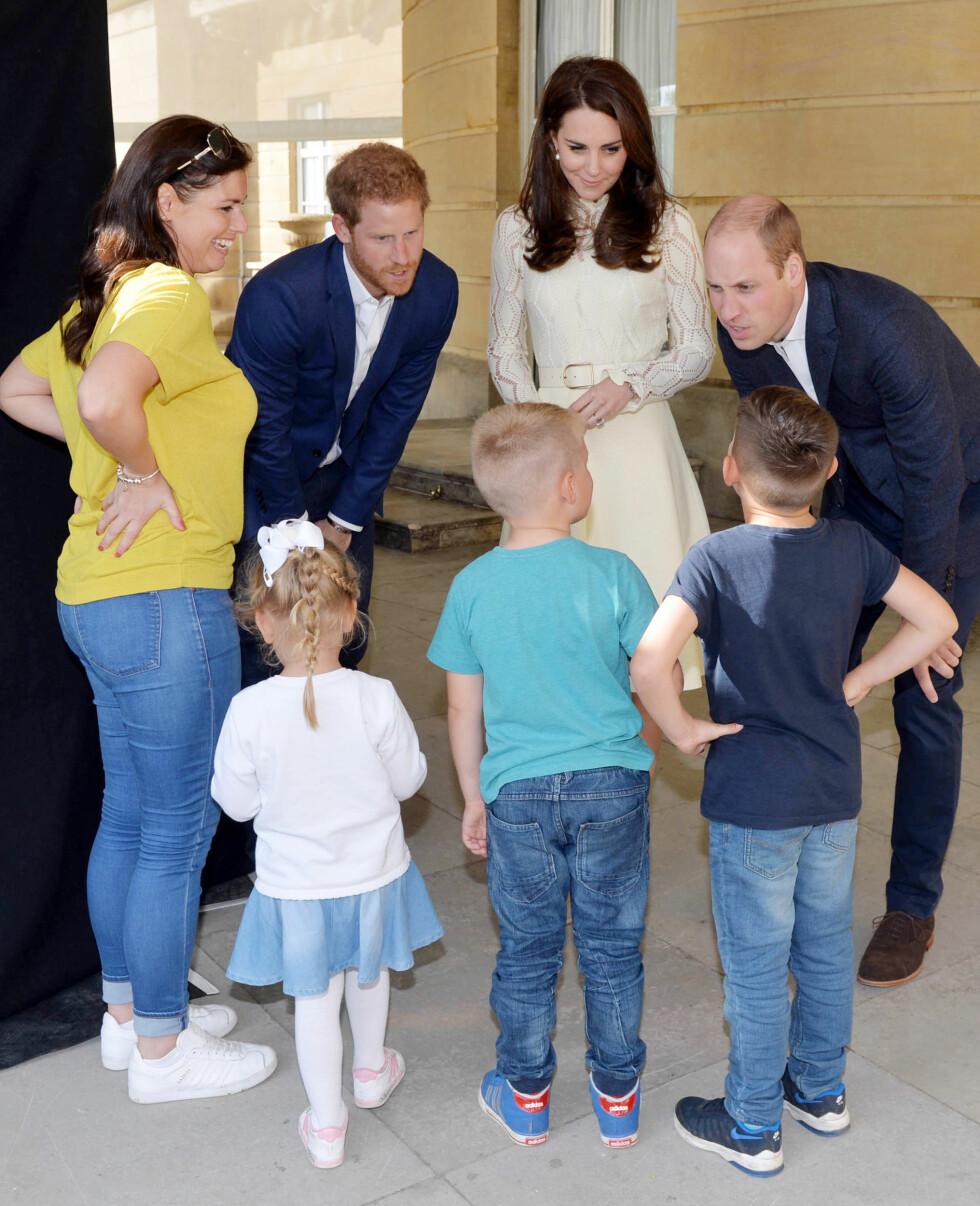 TEA PARTY: Prins Harry, prins William og hertuginne Kate med  Samantha Davidson og hennes tre barn under et teselskap i år på Buckingham Palace i forbindelse med et arrangement for barn og kvinner som har mistet fedre og ektemenn i forbindelse med krigføring. Foto: NTB Scanpix