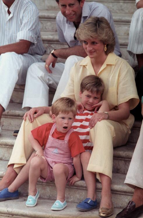HENGIVEN MOR: Prinsesse Diana med sine to sønner, prins William (da 6 år) og prins Harry (da 3 år) fotografert på Palma de Mallorca 9. august 1987. I bakgrunnen pappa prins Charles. Foto: NTB Scanpix