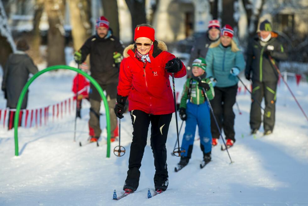SPORTY JUBILANT: Dronning Sonja elsker å gå på ski, og nølte ikke med å ta på seg langrennsskiene da hun og resten av kongefamilien deltok på vinteraktivitetene på Slottsplassen i forbindelse med kongeparets 25-årsjubileum. Kronprins Haakon og kronprinsesse Mette-Marit følger bak. Foto: NTB Scanpix