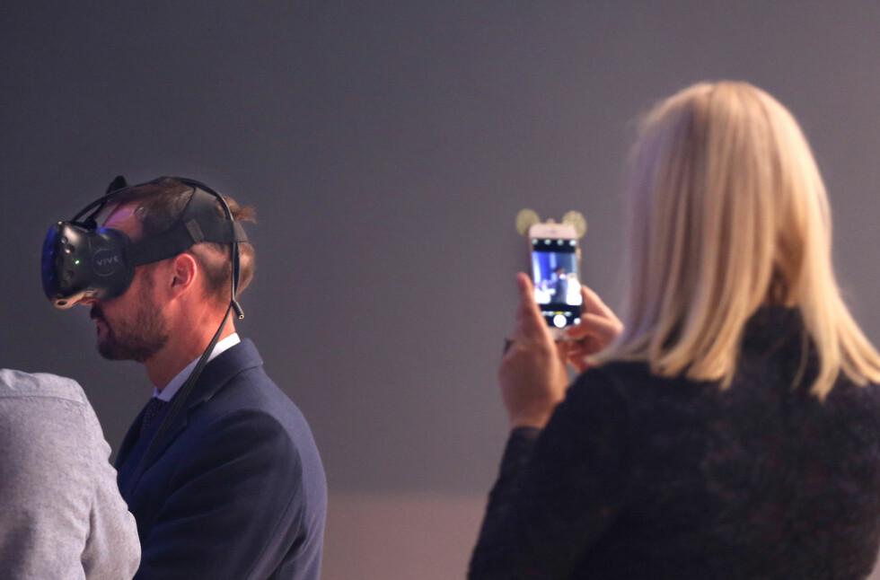 HAAKON SIN TUR: Kronprinsesse Mette-Marit foreviget ektemannen som testet ut VR-brillene under Oslo Innovation Week i oktober. Legg merke til kronprinsessens søte mobildeksel! Foto: NTB Scanpix